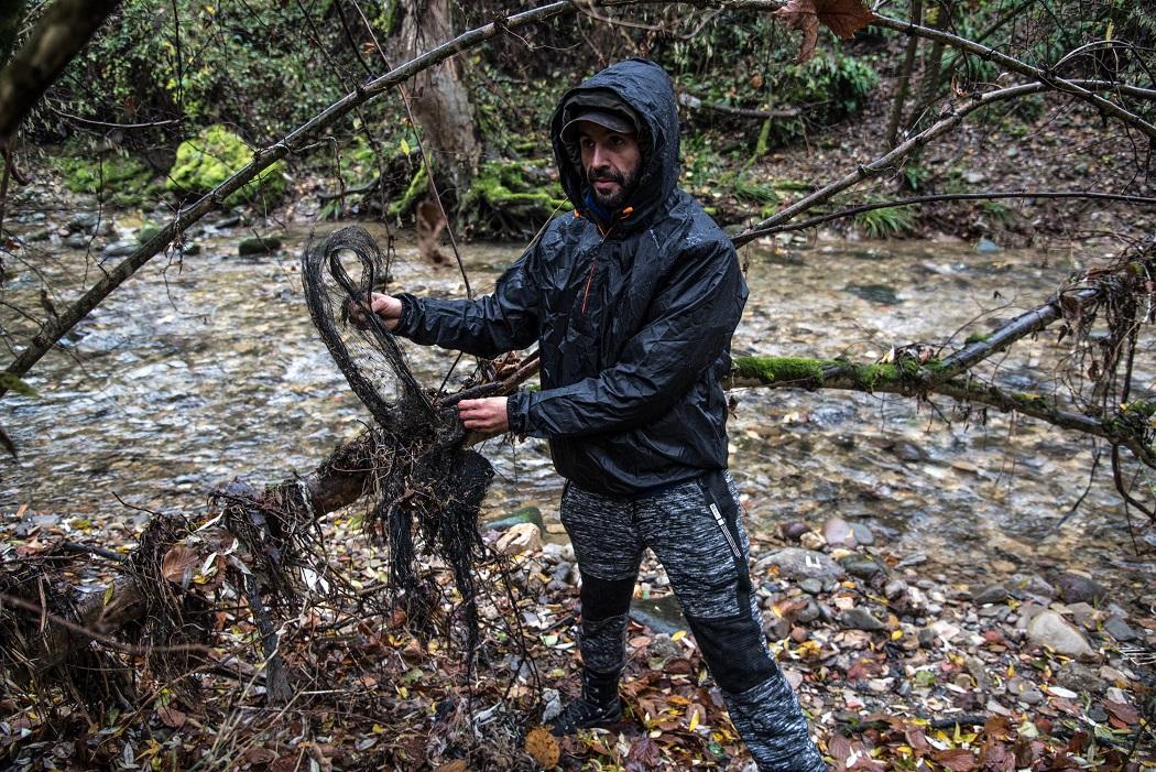 Un ambientalista recupera rifiuti sulle sponde del torrente Uria. © Stefania Prandi